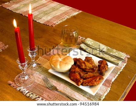 BBQ Chicken wings by  candlelight for lunch - stock photo