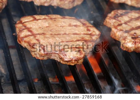 BBQ hamburger on the grill with flames