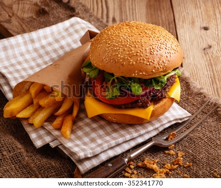 Bbq hamburger on the wooden table with cheese, tomatos, green salad and french fries - stock photo
