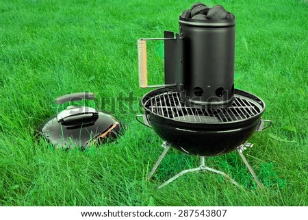 BBQ Kettle Portable Grill Appliance With Charcoal Briquettes Starter On The Summer Lawn, Picnic Or Cookout Concept