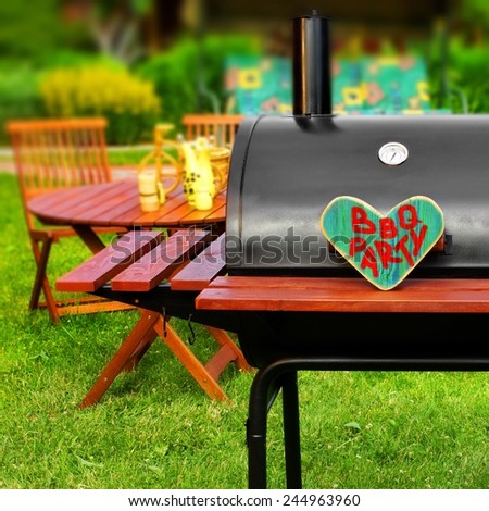BBQ Party Sign on Wooden Heart at Barbecue Appliance on the Backyard at Summertime. Outdoors Furniture on the background. - stock photo