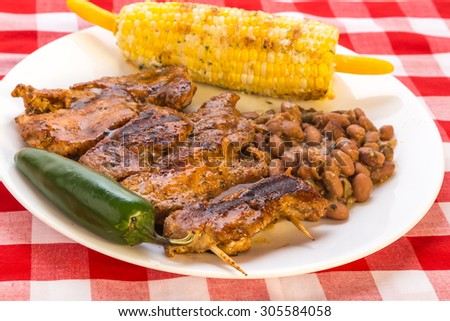 BBQ platter with boneless barbecue ribs on skewers.  Served with roast corn on cob and borracho beans and jalapeno pepper. - stock photo