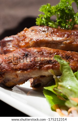BBQ Pork Spare Ribs with french fries and salad In white plate