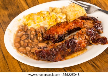 BBQ rib plate with jalapeno corn and borracho beans and tater tot casserole on rustic wooden boards. - stock photo