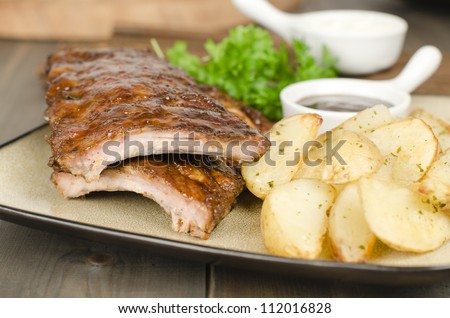 BBQ Ribs - Marinated pork ribs with barbeque dipping sauce and potato wedges with sour cream dip. - stock photo