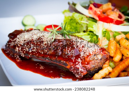 BBQ Ribs - Marinated pork ribs with salad, french fries and barbecue sauce. - stock photo