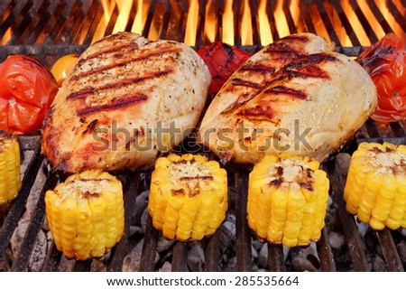 BBQ Roast Chicken Breast With Vegetables On The Hot Flaming Charcoal Grill - stock photo