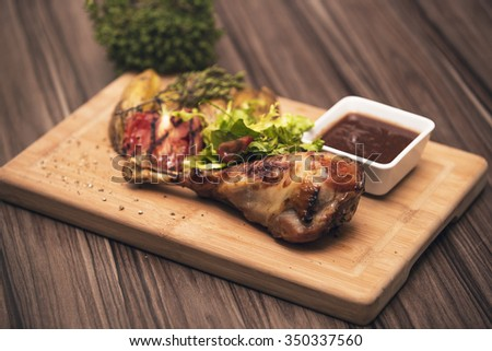 BBQ Roasted Chicken Leg Quarter On The Hot Charcoal Grill Close-up. Crusty goose leg with braised red cabbage and dumplings. Tandoori Chicken.  - stock photo