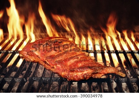BBQ Roasted Pork Baby Back Or Spareribs On The Hot Charcoal Grill With Flames, Closeup
