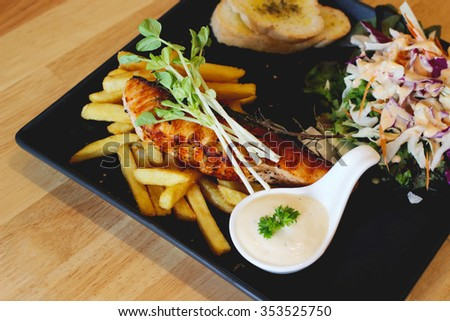 BBQ salmon with salad, french fries and white sauce on black dish