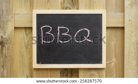 BBQ written on a chalkboard hanging at a wooden wall