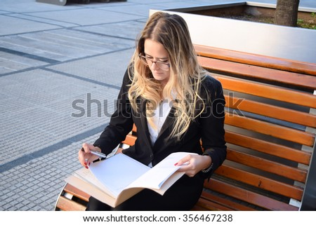 Bbusiness woman working on a bench outside her office. Professional woman on her coffee break. - stock photo