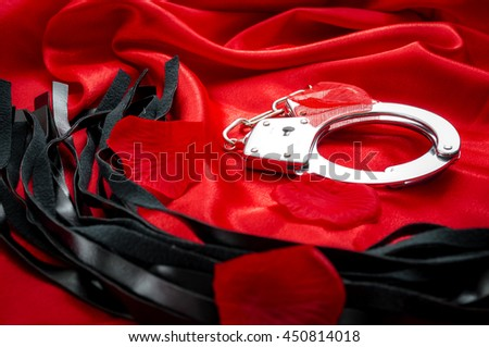 BDSM concept image with hand cuffs and a flogger / whip covered in rose petals on red silk. BDSM is a variety of erotic practices or role playing involving bondage, dominance and submission, masochism