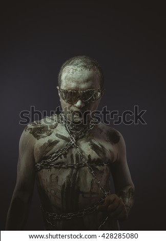 bdsm, man with chains by the body and wire glasses, skin painted black paint and white