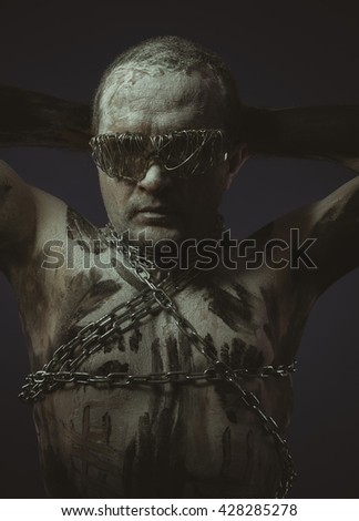 bdsm, man with chains by the body and wire glasses, skin painted black paint and white - stock photo