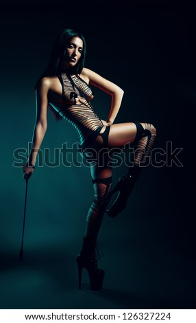 bdsm woman with whip on high heels - stock photo