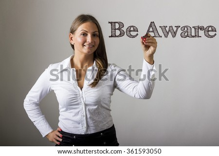 Be Aware - Beautiful girl writing on transparent surface - horizontal image