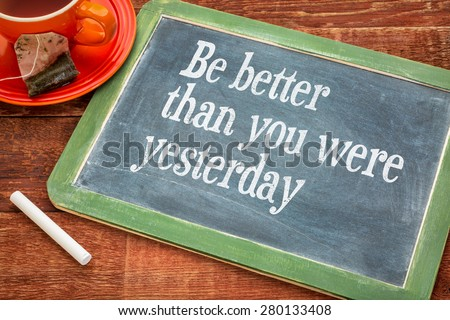 Be better than you were yesterday - motivational text on a slate blackboard with chalk and cup of tea - stock photo