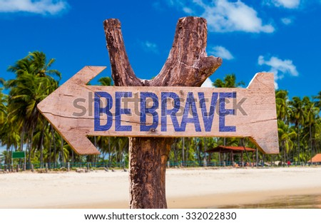 Be Brave arrow with beach background - stock photo