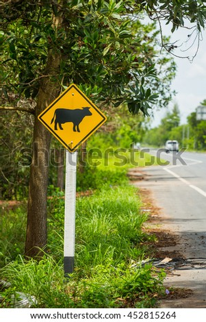 Be careful of the cow yellow traffic sign on the side of the road. - stock photo