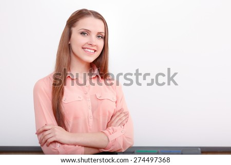 Be confident. Smiling girl with crossed arms on breast on background of white blackboard - stock photo