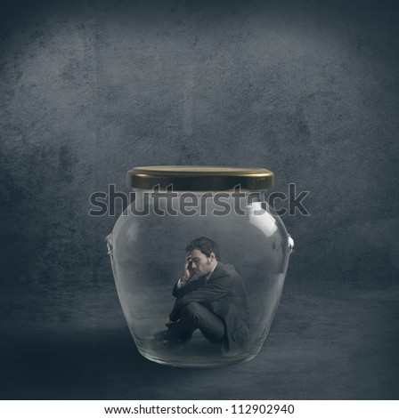 Be ermetic concept with a businessman closed in a jar - stock photo
