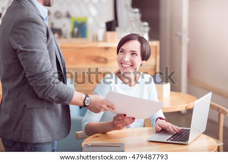 Be friendly. Cropped image of two smiling co-workers working together with papers and using laptop