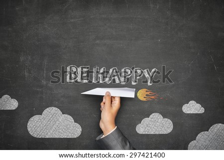 Be happy concept on black blackboard with businessman hand holding paper plane - stock photo