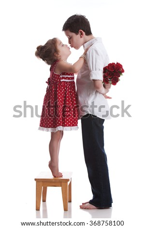 Be Mine.  Adorable toddler standing on her tip-toes trying to kiss a young boy that is holding a bouquet of flowers behind his back.  Isolated on white.   - stock photo