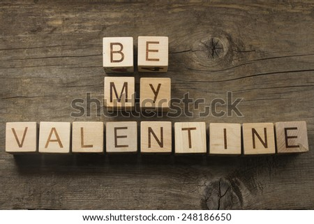 be my valentine text on a wooden cubes on a wooden background - stock photo
