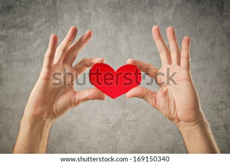 Be my Valentine, Valentines day concept. Man holding red paper heart in his hands - stock photo