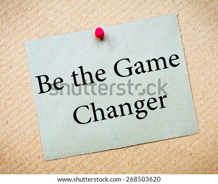 BE THE GAME CHANGER Message. Recycled paper note pinned on cork board. Concept Image - stock photo