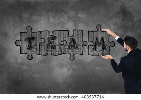 Be the team! Rear view of young man in full suit touching concrete wall with illustrated puzzle on it   - stock photo