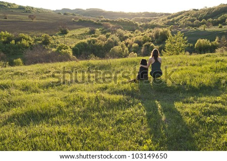 Be?utiful young woman and her dog watch sunset together - stock photo