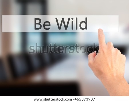Be Wild - Hand pressing a button on blurred background concept . Business, technology, internet concept. Stock Photo