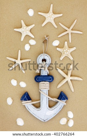Beach abstract background with decorative wooden anchor, starfish and cockle sea shells on sand. - stock photo