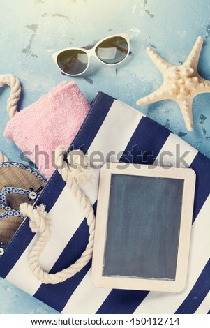 Beach accessories. Bag with flip-flops and towel and blackboard for your text on stone background. Top view with copy space. Sunny toned