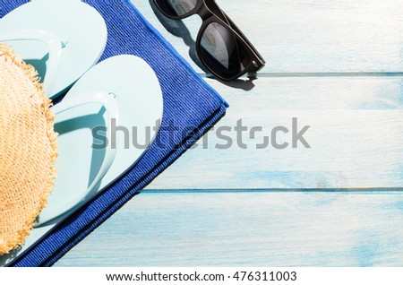 beach accessories. stylish sunglasses with flip flops, hat and towel on blue wooden table