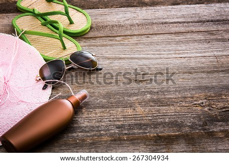 Beach accessories. Summer shoes and hat with sunglasses and suntan lotion on a wooden background - stock photo