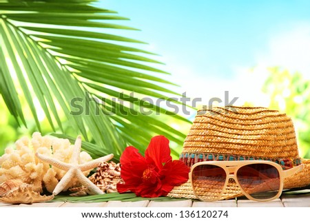 Beach accessories with straw hat,sunglasses and seashells. - stock photo