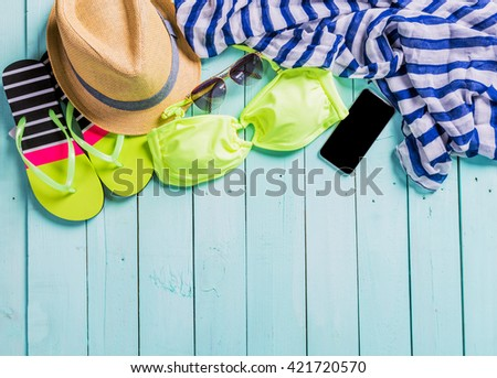 Beach accessories with yellow swimming suit,sunglasses and flip flops - stock photo