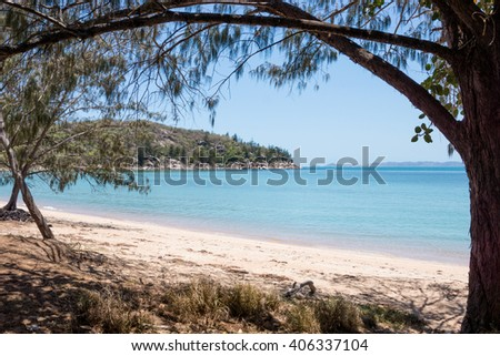 Beach and blue sea framed by trees on tropical Magnetic Island, Australia - stock photo
