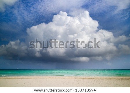 Beach and boat in distance with heavy clouds - stock photo
