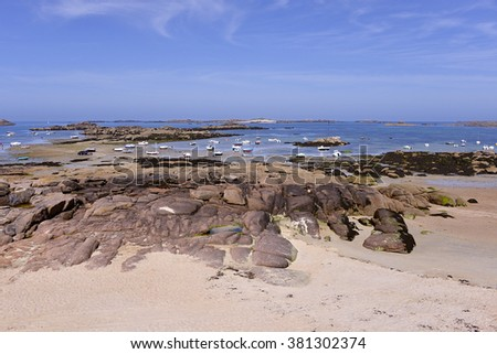 Beach and boats at low tide on the Pink Granite Coast (cote de granite rose in french) at Trebeurden, commune in the Cotes-Armor department of Brittany in northwestern France. - stock photo