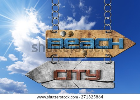 Beach and City - Directional Signs. Wooden directional sign with two arrows in opposite direction hanging with metal chain, with text beach and city on blue sky with clouds and sun rays - stock photo