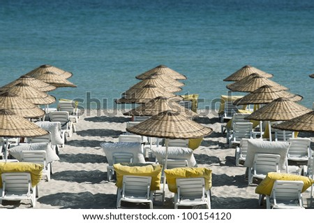 beach and empty lounge chairs by the blue sea - stock photo