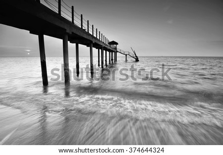 Beach and jetty in black and white. - stock photo