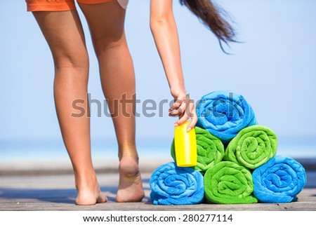 Beach and summer vacation accessories concept - close-up of colorful towels, hat, bag and sunblock - stock photo