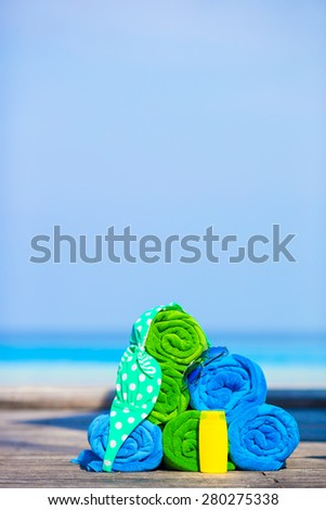 Beach and summer vacation accessories concept - close-up of colorful towels, swimming goggles and sunblock - stock photo