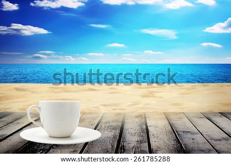 Beach and table with cup of coffee - stock photo